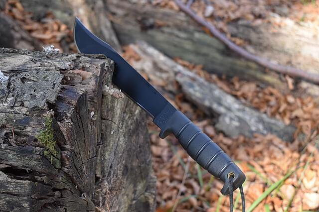 Survival Messer steckt im Holz.